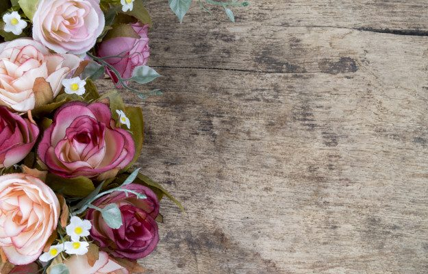 Vintage rose flowers on rustic wooden background. Copy space.